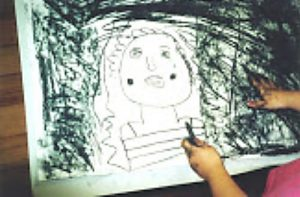 Young child drawing with natural charcoal